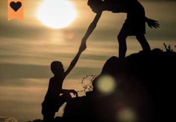 image of one person helping another person climb up a hill