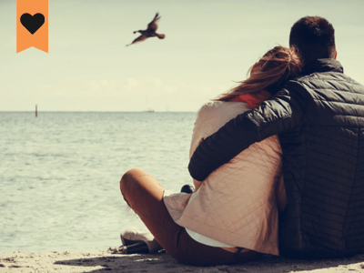 man and woman sitting close on a beach watching a bird fly by