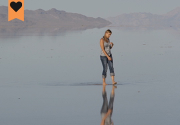 woman walking on a lake shore with her reflection showing in the water and desert hills in the background