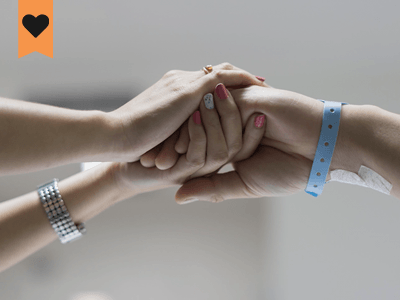 females holding hands two of which have hospital bands on thier wrists while a third females hand is resting on top