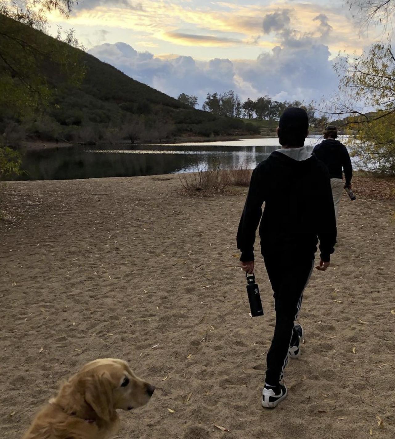 Boys hiking at lake with dog