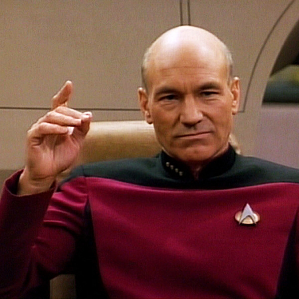 Captain Picard in his captain's chair with his right hand pointing into the air before saying, Engage.