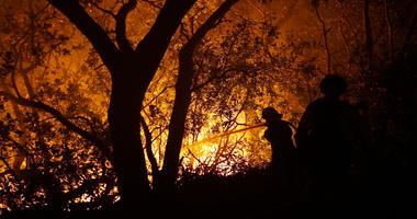 Firefighter Paige Madrid hoses down an approaching wildfire near Kenwood in Sonoma County