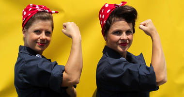 "Jessica Curtis and Sarah Neller pose for a photograph in front of a ""We Can Do It"" backdrop"