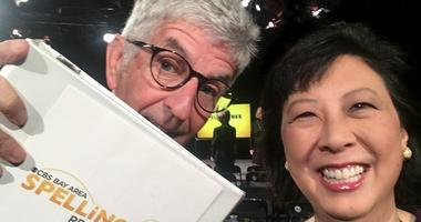 Stan Bunger holds spelling bee word book while posing with Sharon Chin