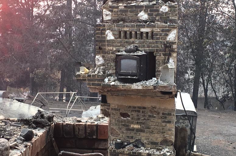Chimney with wood stove insert in rubble of home in Paradise, CA