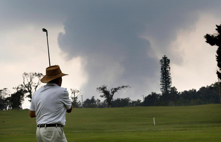 Ken McGilvray, of Keaau, Hawaii, golfs in Volcano, Hawaii as ash from the summit crater of Kilauea volcano rises in the background, Wednesday, May 16, 2018.