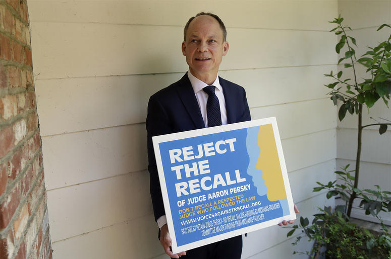 In this May 15, 2018 file photo, Judge Aaron Persky poses for a photo with a sign opposing his recall in Los Altos Hills, Calif. Northern California voters are deciding on Tuesday, June 5 whether to remove Persky from office for the first time in decades