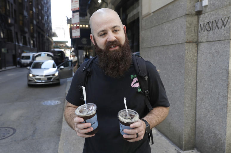 Adam Taylor, a sound engineer from Las Vegas carries two glasses of iced coffee, responds to a question about new research showing that drinking coffee may boost chances for a longer life, even for those who down at least eight cups daily Monday, July 2,