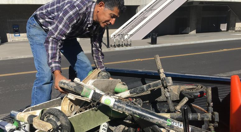 Roger Castillo, who monitors South Bay rivers, examines Bird scooters pulled from the Guadalupe River in April 2019.