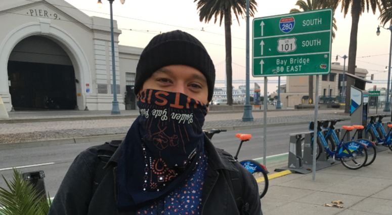 A pedestrian in San Francisco tries to protect himself against the unhealthy air quality that has enveloped the area.