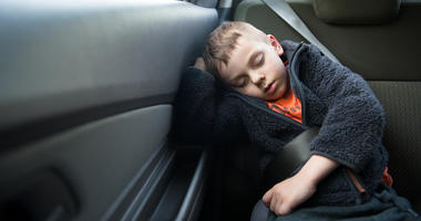 Adorable sleeping child on the back seat of the car with safety belt...