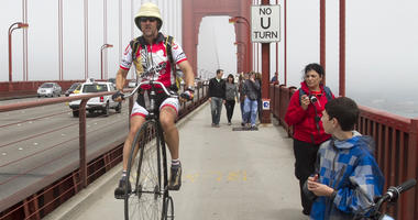 Steve Meagher, left, rides a penny farthing bicycle across the Golden Gate Bridge in San Francisco, California, Saturday August 13, 2011. Meagher, of Orinda, California, rode the high wheel bicycle from Lake Tahoe to San Francisco for his 47th birthday, a