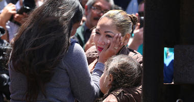 Isela Michel Zavala wipes a tear from her mother Yudridia Guadalupe Zavala, whose arm is draped over Isela's daughter Briana Montes, as they meet in the Door of Hope at Borderfield State Park in San Diego on April 30, 2016. The Door of Hope was opened for