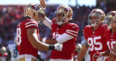 San Francisco 49ers tight end Garrett Celek, left, is greeted by quarterback Jimmy Garoppolo, center, after scoring a touchdown