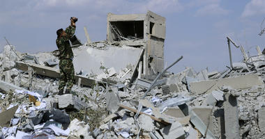 A Syrian soldier films the damage of the Syrian Scientific Research Center which was attacked by U.S., British and French military strikes to punish President Bashar Assad for suspected chemical attack against civilians, in Barzeh, near Damascus, Syria, S