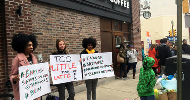Protesters gather outside a Starbucks in Philadelphia, Sunday, April 15, 2018, where two black men were arrested Thursday after Starbucks employees called police to say the men were trespassing. The arrest prompted accusations of racism on social media. S