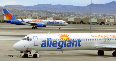 """In this May 9, 2013, file photo, two Allegiant Air jets taxi at McCarran International Airport in Las Vegas. Shares of Allegiant Air's parent company are tumbling in Monday, April 16, 2018, premarket trading following a """"60 Minutes"""" investigation that ex"""