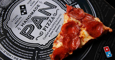 FILE - This Oct. 21, 2016, file photo shows a slice of pepperoni pizza on a Domino's Pizza box in Derry, N.H. Fla. The pizza chain said Monday, April 16, 2018, that its drivers can meet customers at beaches, parks and landmarks to hand over pizza, cheesy