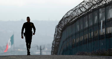 In this June 22, 2016 file photo, Border Patrol agent Eduardo Olmos walks near the secondary fence separating Tijuana, Mexico, background, and San Diego in San Diego. California has rejected the federal government's initial plans for National Guard troops