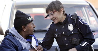 In this March 12, 2015, file photo, Seattle police officer Debra Pelich, right, wears a video camera on her eyeglasses as she talks with Alex Legesse before a small community gathering in Seattle. While the Seattle Police Department bars officers from usi
