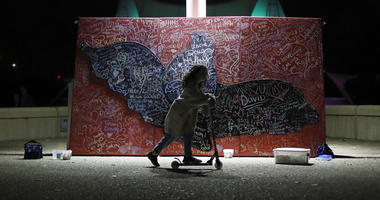 In this Oct. 15, 2017, file photo, a child plays beside a message board adorned with notes for loved ones who took their own lives during an Out of the Darkness Walk event organized by the Cincinnati Chapter of the American Foundation for Suicide Preventi