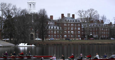 In this March 7, 2017 file photograph, rowers pass the campus of Harvard University as they paddle down the Charles River in Cambridge, Mass. Harvard and the group Students for Fair Admissions will file dueling analyses of the Ivy League school's admissio