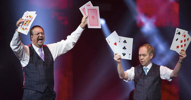 "In this Dec. 1, 2017, file photo, Penn Jillette, left, and Raymond Teller perform their ""Penn & Teller"" act at the Vegas Strong Benefit concert in Las Vegas. The duo cancelled a performance scheduled for Friday, July 6, in Biloxi, Miss., because Teller's"