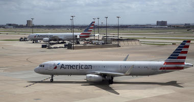 In this June 16, 2018 file photo, American Airlines aircrafts are seen at Dallas-Fort Worth International Airport in Grapevine, Texas. American Airlines says it will stop using plastic straws and drink stirs and replace them with biodegradable alternativ