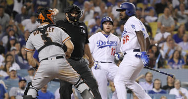 San Francisco Giants catcher Nick Hundley, left, reacts to being shoved by Los Angeles Dodgers' Yasiel Puig, right, as they argue while home plate umpire Eric Cooper, second from left, gets between them and Max Muncy runs in during the seventh inning of a
