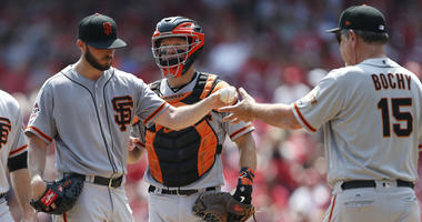 San Francisco Giants starting pitcher Andrew Suarez, left, is pulled from the game by manager Bruce Bochy, right during the third inning of a baseball game against the Cincinnati Reds, Sunday, Aug. 19, 2018, in Cincinnati. At rear is Giants catcher Nick H
