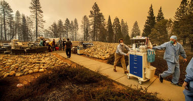 Medical workers move equipment from a makeshift emergency room while the Feather River Hospital burns as the Camp Fire rages through Paradise, Calif., on Thursday, Nov. 8, 2018