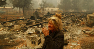 - In this Nov. 9, 2018 photo, Cathy Fallon reacts as she stands near the charred remains of her home in Paradise, Calif