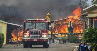 Firefighters wait for water as they battle flames at the Alpine Oaks Estates mobile home park during a wildfire Friday, July 6, 2018, in Alpine, Calif. Gusty winds fanned the flames as Southern California struggles through a scorching heat wave.