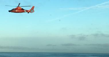 A helicopter flies above the Pacifica coastline, searching for a missing swimmer on March 26, 2019.