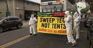Demonstrators in hazmat suits protested Google plans for a San Jose office complex by obstructing a shuttle bus for tech workers.