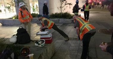 Construction workers stretch before starting their shift