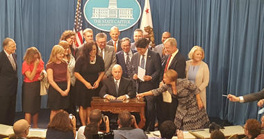 Gov. Jerry Brown, seated, signed legislation that forces California to get all of its power from renewable sources by 2045.