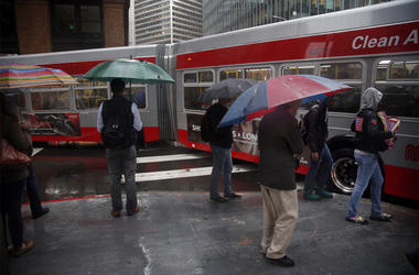 Bus riders and pedestrians brave the storm with rain pouring down in the Financial District of San Francisco on Friday, Oct. 14, 2016. (Photo by Karl Mondon/Bay Area News Group/TNS)