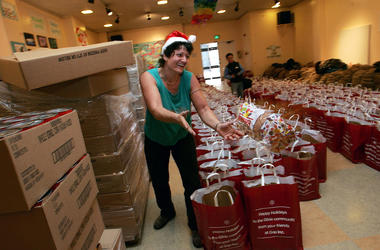 SAN FRANCISCO - DECEMBER 16: A volunteer tosses a loaf of bread that will be put into grocery bags to be distributed to the needy at Glide Memorial Church December 16, 2004 in San Francisco. The church hopes to pass out 8,000 grocery bags to people in nee