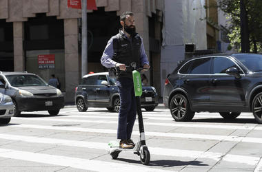 A man rides a motorized scooter as he approaches Market Street in San Francisco.