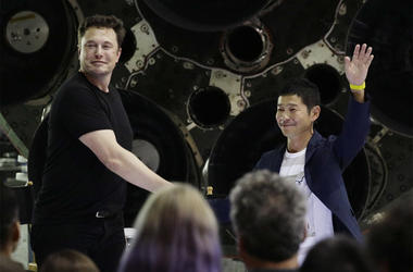 SpaceX founder and chief executive Elon Musk, left, shakes hands with Japanese billionaire Yusaku Maezawa, right, after announcing him as the first private passenger on a trip around the moon, Monday, Sept. 17, 2018, in Hawthorne, Calif. (AP Photo/Chris C