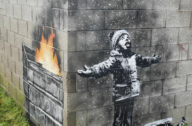 In this file photo dated Dec, 20, 2018, showing an artwork by Banksy on the side of a garage depicts a child dressed for snow playing in the falling ash and smoke from a skip fire, in Port Talbot, Wales. The artwork has been sold to an Essex art dealer fo