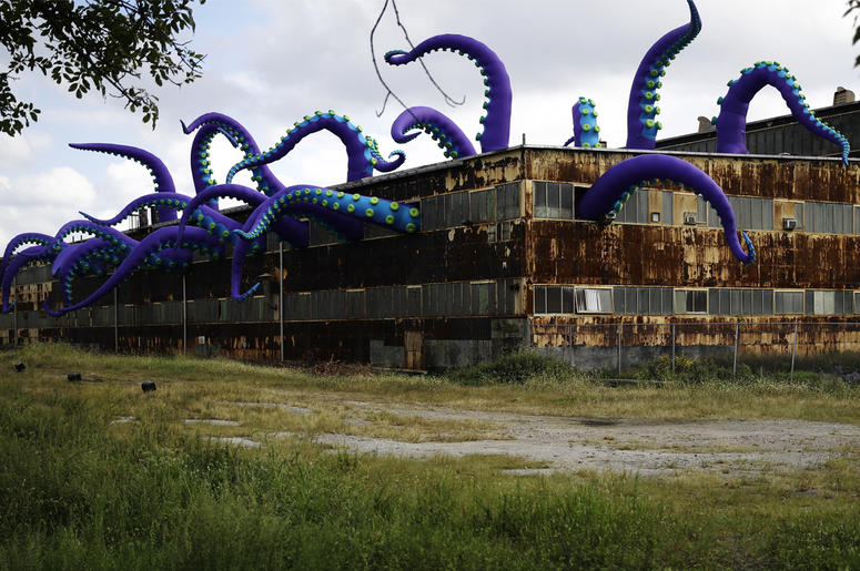 """An inflatable sculpture entitled """"Sea Monsters HERE"""" extends from a rusting warehouse called Building 61 at the Navy Yard in Philadelphia, Tuesday, Oct. 9, 2018. The installation was created by UK-based artists Filthy Luker and Pedro Estrellas. The former"""