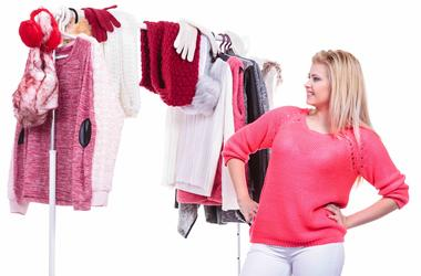 Woman choosing clothes to wear from her closet