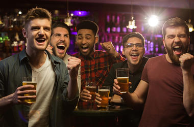 Four happy men holding beer mugs and gesturing while watching TV in bar or pub (Photo credit: Vadymvdrobot/Dreamstime)