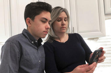 Grant Thompson and his mother, Michele, look at an iPhone