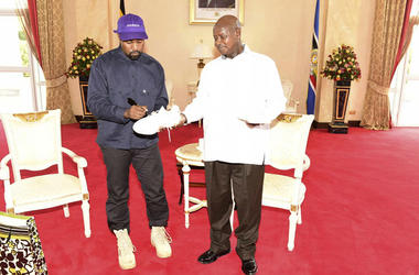 Kanye West autographs a pair of his sneakers as a gift to Uganda's President Yoweri Museveni