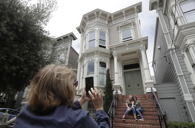 "Aries Layton, seated left, and her aunt Kelsy Layton pose as Debra Layton, Aries' grandmother and Kelsy's mother, foreground, takes photos outside a Victorian home made famous by the television show ""Full House"" in San Francisco, Tuesday, July 17, 2018. T"