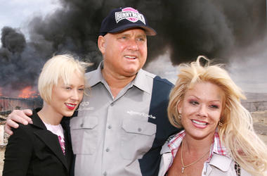 "In this March 25, 2007, file photo, Moonlite Bunnyranch brothel owner Dennis Hof poses with two of his ""working girls"" Brooke Taylor, left, and a woman working under the name ""Airforce Amy"", right, as firefighters burn down remains of the former Mustang R"